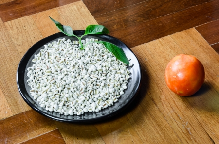 paquet: close up lot of white millet on dish with red tomato  at brown wood paquet floor ground Stock Photo