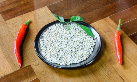 paquet: close up lot of white millet on dish with two pepper at brown wood paquet floor ground