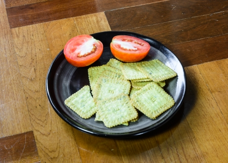 paquet: many biscuits desert and tomato cut on single black dish at brown wood paquet floor ground