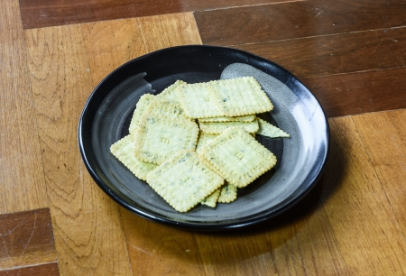 paquet: close up biscuits desert  on single black dish at brown wood paquet floor ground Stock Photo