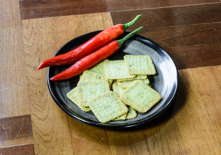 close up biscuits desert  and pepper on single black dish at brown wood paquet floor ground photo