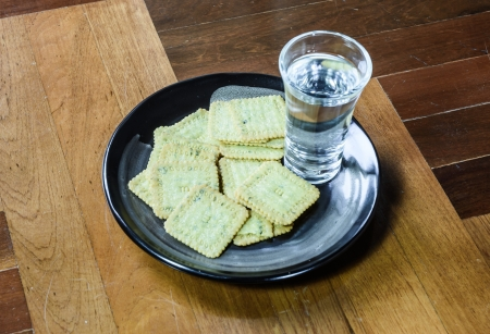 paquet: close up biscuits desert  and clear water on single black dish at brown wood paquet floor ground