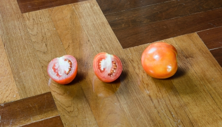 paquet: many tomato cut and single tomato at brown wood paquet floor ground