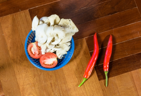 paquet: top view mushroom and tomato in basket  with two pepper at wood paquet background