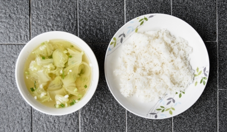 top view green lettuce and meat soup thailand style food in bowl with rice on grey tile background photo