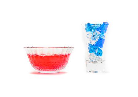 single red strawberry jelly in small dishware glass with ice cube isolated on white background photo