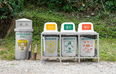 Grunge yellow green and red bin on stand  for recycle with thai language in public park photo