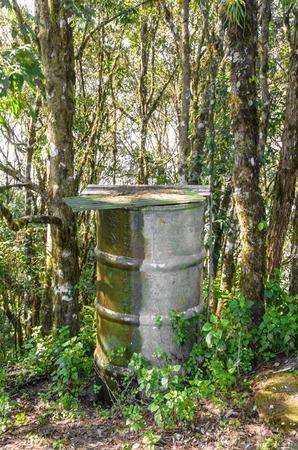 dep�sito agua: peque�o tanque de agua de acero del grunge de edad para la gira generales la gente en los bosques naturales en Thailnad monta�a