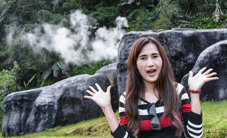 happy and smile asia young woman travel on hot spring naturl with smoke on the stone photo