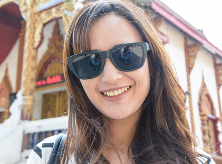 trustful: Close up portrait of a asia young womans wear sunglasses with a  blurred outdoor .