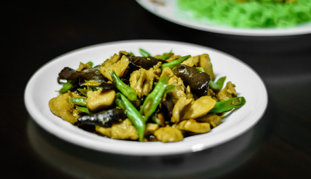 Fried oil with pork, mushroom and cow-pea food on white dish photo