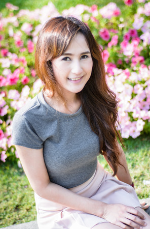 portrait asia young woman smile on summer outoor at flower garden photo