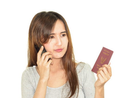 asia young woman use mobile phone and holding thailand passport isolated on white photo