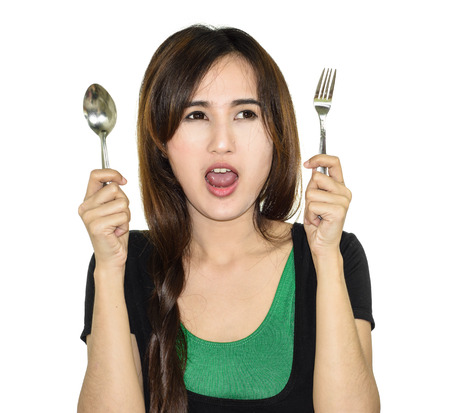 asia young hungry woman hold spoon and fork isolated on white background photo