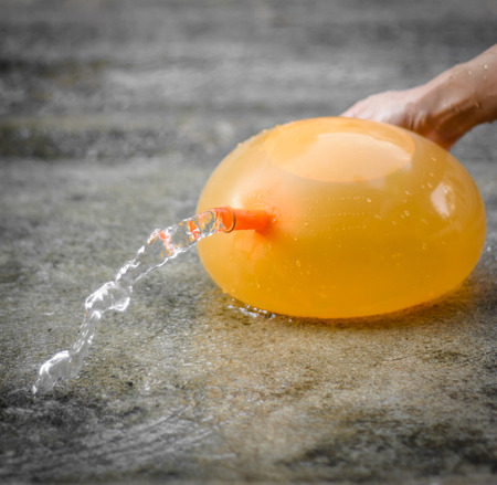 gilr hand paly and hold yellow water balloon at outdoor background photo