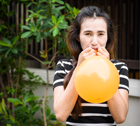 asia young girl is inflating balloon at outdoor  photo