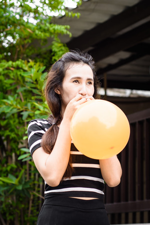 inflating: asia young girl is inflating balloon at outdoor  Stock Photo