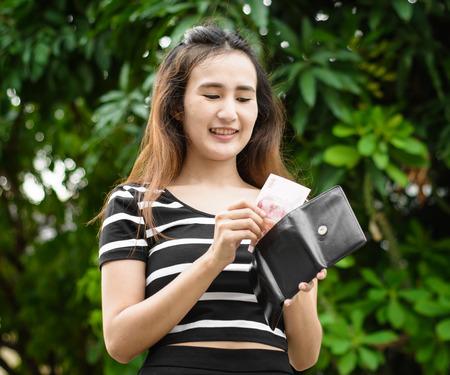 pick money: joven asia recoger el dinero y la cartera que re�nan al fondo natural al aire libre Foto de archivo