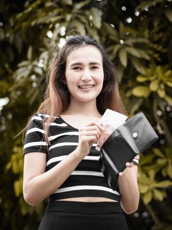 pick money: joven asia recoger el dinero y la cartera que sostiene con filtro retro en fondo natural al aire libre Foto de archivo