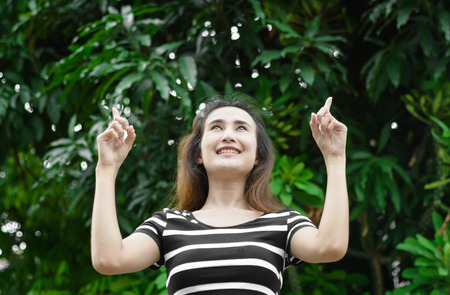 Young asian woman pointing up with finger to high tree at outdoor natural background photo