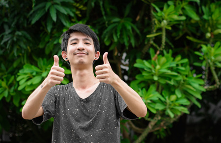Happy male asia showing thumbs up at outdoor on natural background photo