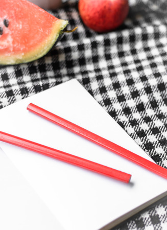 note book and pencil with fruit on plaid fabric photo