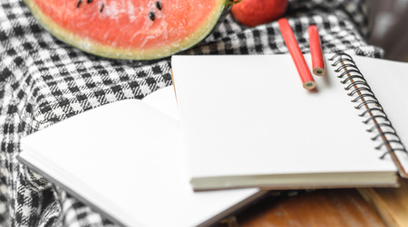 note book and pencil with fruit on plaid fabric pattern background photo