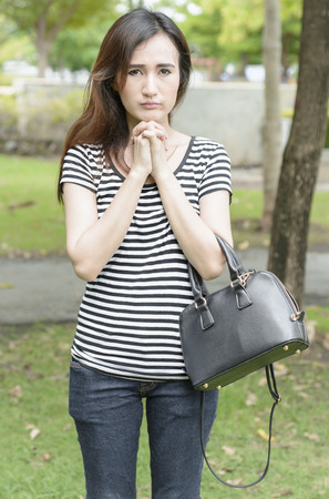 Young woman so sad with  fashion bags at outdoor natural on summer photo