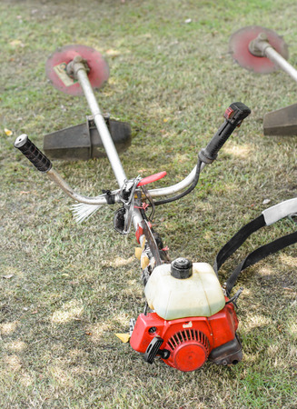 the lawn mower machine at outdoor sunrise on green grass field photo