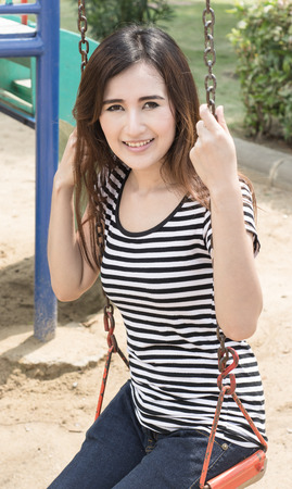 asian Portrait of a beautiful happy girl on a swing  at Outdoors summer photo
