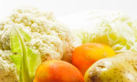 Fresh tomato,Cauliflowers and potato vegetable at wood plate on white light pattern background photo
