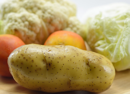 Fresh potato and vegetable at wood plate on white light pattern background photo