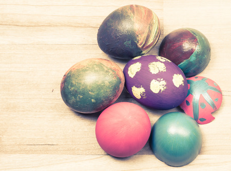 many colorful Easter eggs on wooden background with retro filter photo