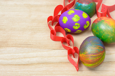 colorful Easter eggs and ribbon heart decoration on wooden background photo