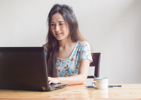 asian business woman working with laptop at wood table photo