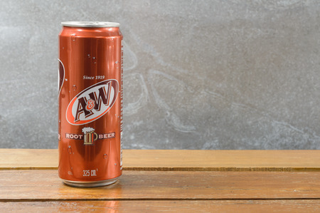 root beer: bangkok,THAILAND - october 05, 2014: Slim a&w root beer can on wood table.  a&w is produced and manufactured by  The Coca-Cola Company.