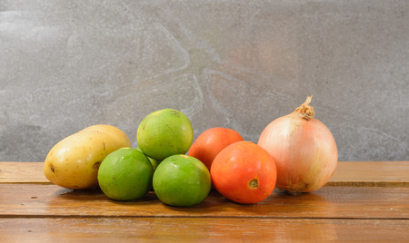 Fresh limes,onion,potato and tomato vegetable on wood table photo