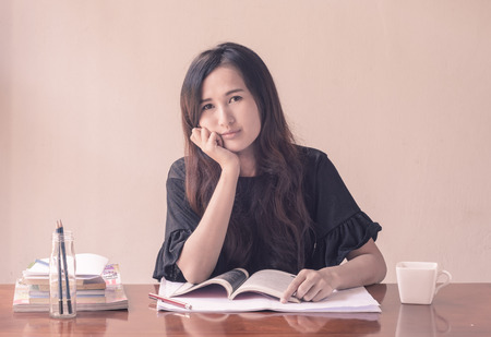 asian Woman is working and reading a  book with retro filter photo