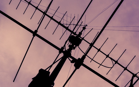 signal pole: silhouette of Tv Antenna at sky with retro filter