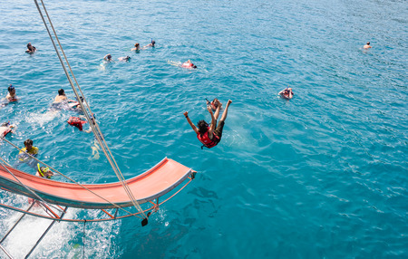 play popular: Koh chang Trat,THAILAND - December 29, 2014:  Unidentified Travel tourist People play sliding on the boat at sea. koh chang is very popular tourist destination for holidays at koh chang Trat, Thailand . Editorial