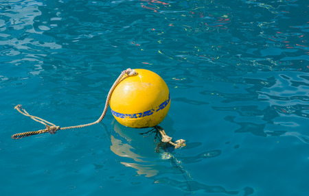 old yellow buoy in the natural sea photo