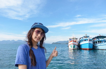 portrait happy asia woman show thumb up on natural sea photo