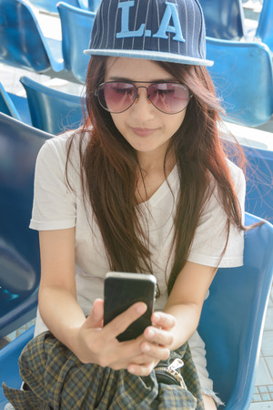 young Asian woman using smartphone at outdoor summer