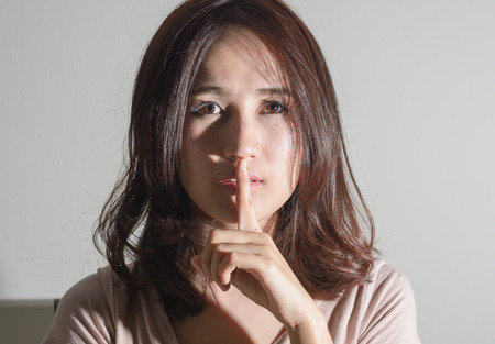 portrait asia woman doing a silence sign with lighting shadow  on wall photo