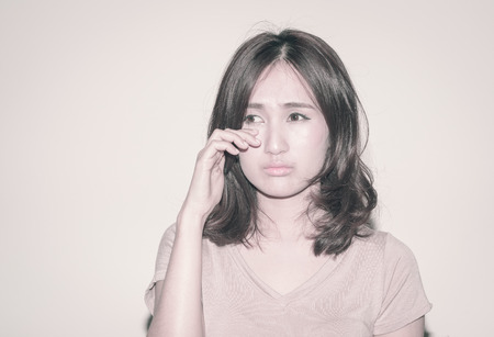 asia woman sad and crying on wall with retro filter photo