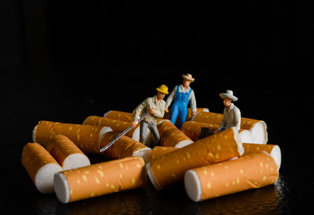lot of cigarette butt with miniatures workers on black photo