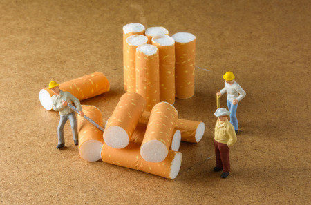 cigarette butt with miniatures workers on wood with selective focus photo