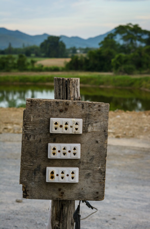 electric fixture: electrical plug on wood pole at outdoor natural Stock Photo
