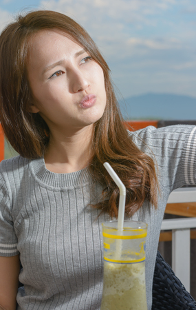 sipping: asia woman sipping a milkshake drink at outdoor balcony