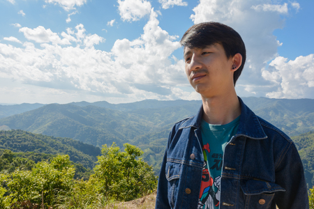 aisa: aisa man relax at outdoor on top of mountain natural hill